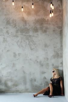 Blonde vrouw met vleermuisvormig masker voor halloween of maskerade en zwart kostuum