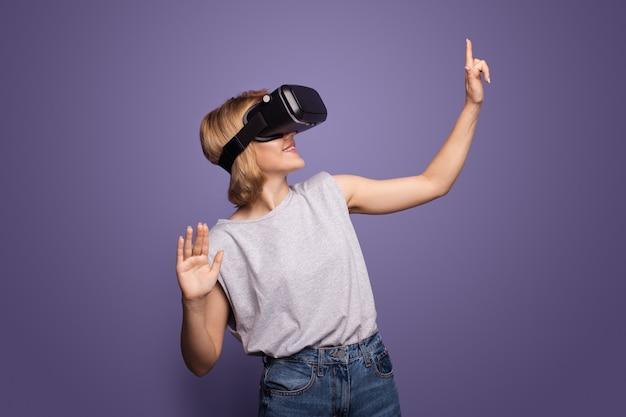 Blonde vrouw met vr-headset raakt iets aan terwijl ze poseren op een violette muur