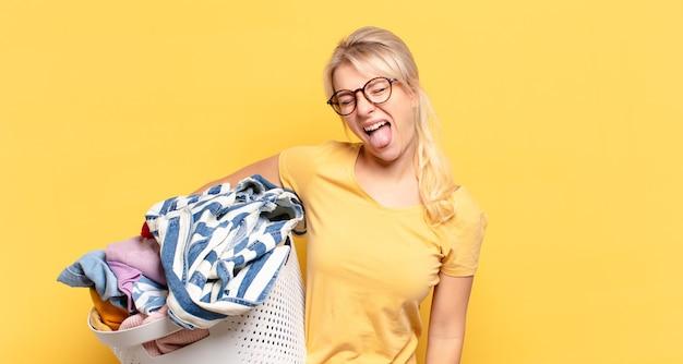 Blonde vrouw met vrolijke, zorgeloze, rebelse houding, grappen maken en tong uitsteken, plezier maken
