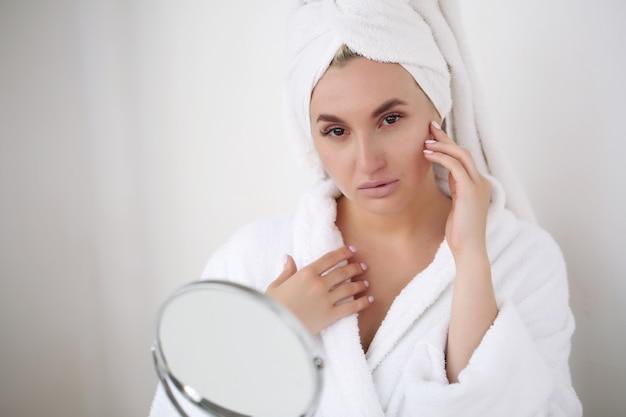 Blonde vrouw na bad in witte badjas en handdoek