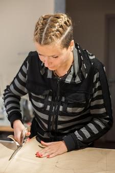 Blonde vrouw naaister bezuinigingen van kraft papier patroon voor het maken van kleding