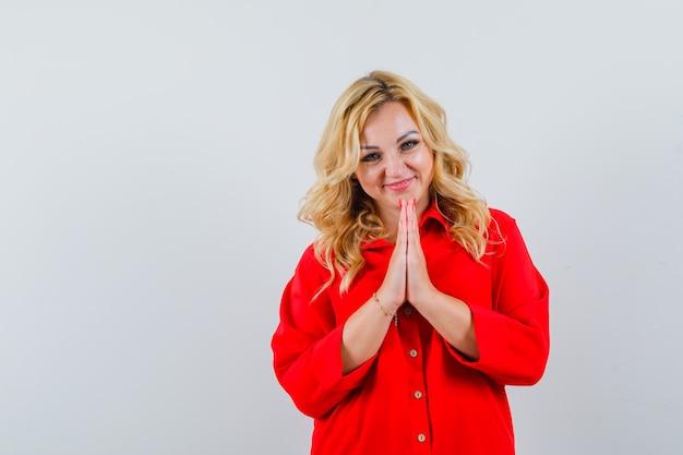 Blonde vrouw namaste gebaar in rode blouse tonen en gelukkig kijken.