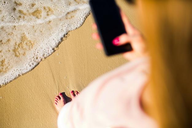 Blonde vrouw neemt foto van haar voeten die staan voor schuimende golven