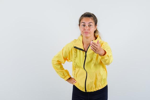 Blonde vrouw nodigt uit om te komen terwijl ze hand op taille in geel bomberjack en zwarte broek houdt en er mooi uitziet