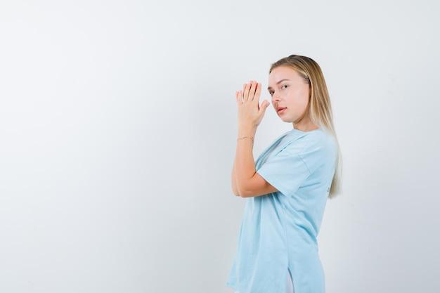 Blonde vrouw omklemde handen voor gezicht, kijkend over schouder
