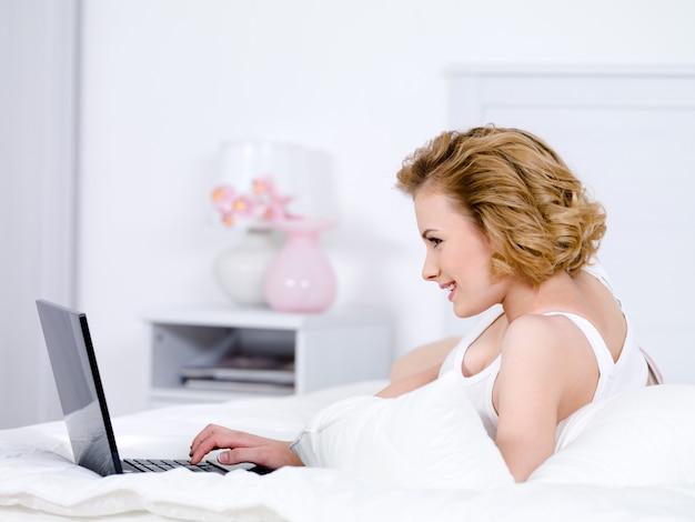 Blonde vrouw op een bed met laptop