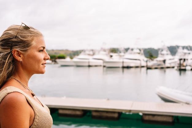 Blonde vrouw op een pier die naar afgemeerde jachten kijkt