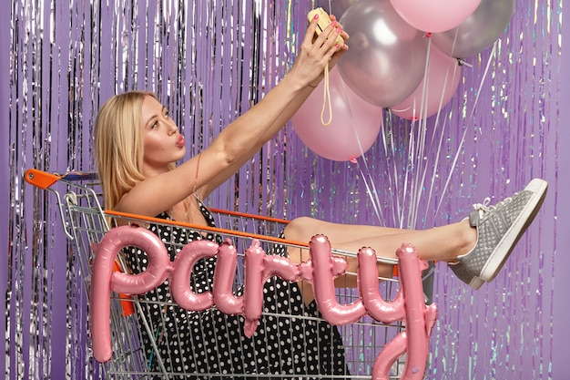Blonde vrouw op feestje in winkelwagen met ballonnen