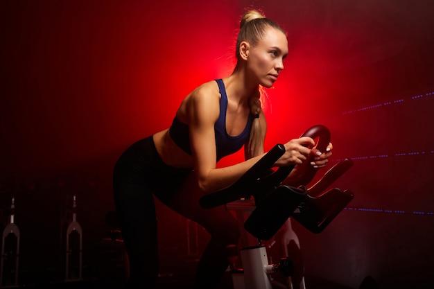 Blonde vrouw op fiets trainen op sportschool in rokerige ruimte, geconcentreerd op training