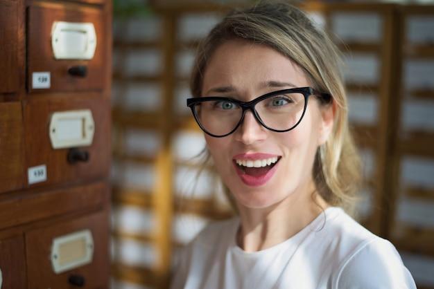 Blonde vrouw opgewonden meningsuiting in de bibliotheek