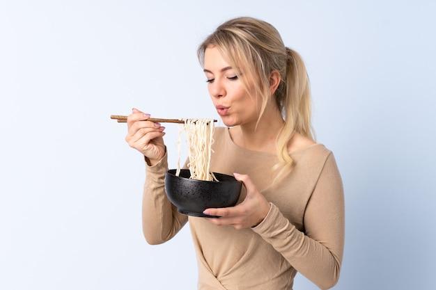 Blonde vrouw over geïsoleerd blauw die een kom noedels met eetstokjezand houdt dat het blaast omdat zij heet zijn