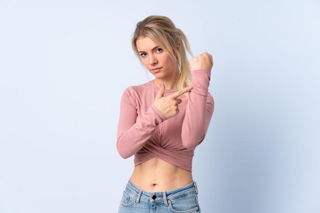Blonde vrouw over geïsoleerde blauwe muur die het gebaar maakt te laat te zijn