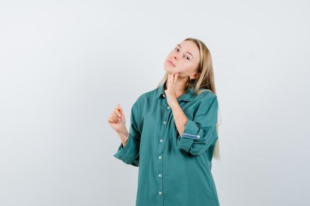 Blonde vrouw poseert terwijl ze haar kin aanraakt in een groen shirt en er charmant uitziet