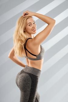Blonde vrouw poseren in trendy grijze sportkleding