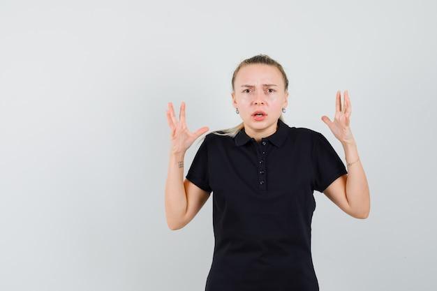 Blonde vrouw praten over telefoon in zwart t-shirt en peinzend op zoek
