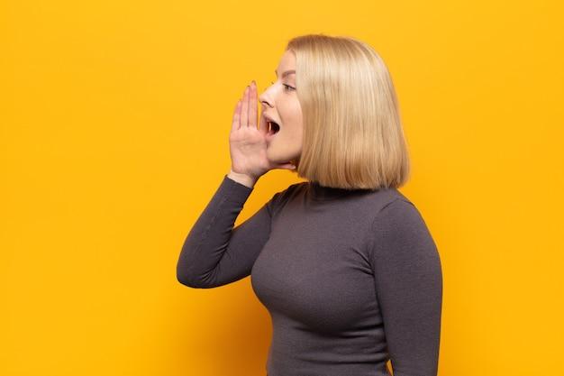 Blonde vrouw profielweergave, blij en opgewonden kijkend, schreeuwend en bellend om ruimte aan de zijkant te kopiëren