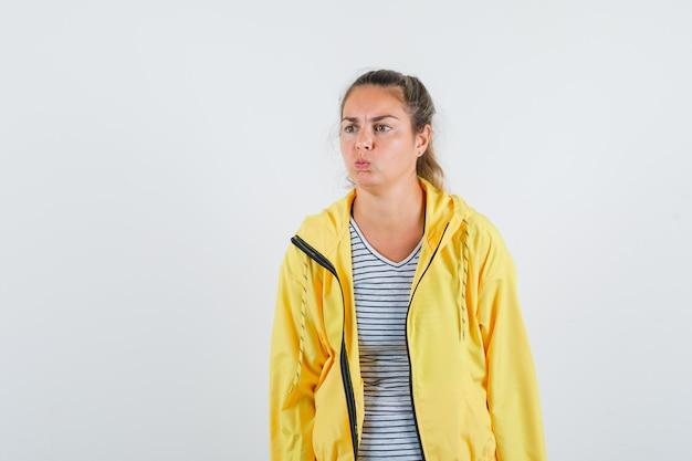 Blonde vrouw puffende wangen in geel bomberjack en gestreept overhemd en peinzend op zoek