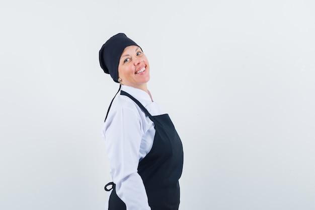 Blonde vrouw rechtop en poseren aan de voorkant in zwarte uniforme kok en ziet er mooi uit.