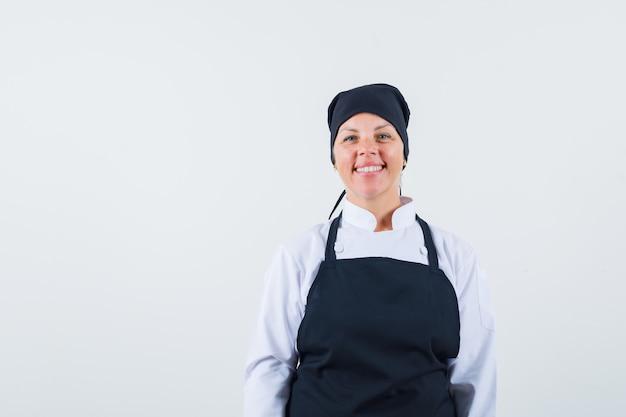 Blonde vrouw rechtop, glimlachend en poseren voor de camera in zwarte kok uniform en ziet er mooi uit. vooraanzicht.