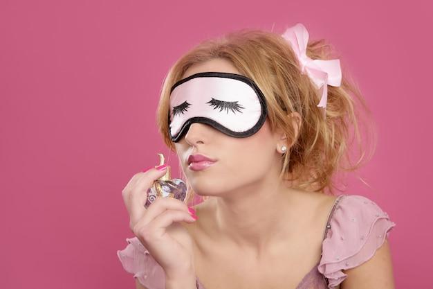 Blonde vrouw ruikende parfum slaap masker blind