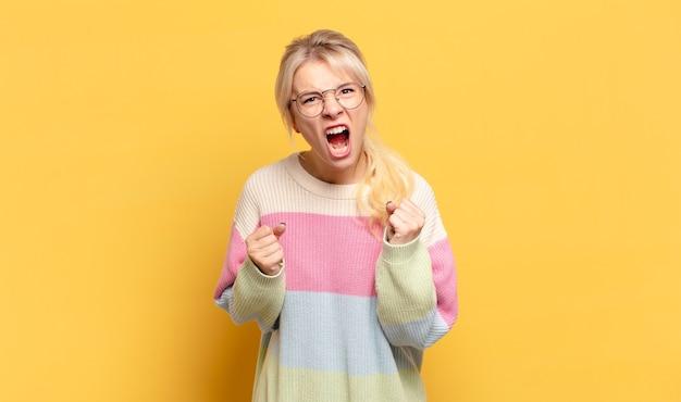 Blonde vrouw schreeuwt agressief met geïrriteerde, gefrustreerde, boze blik en strakke vuisten, zich woedend
