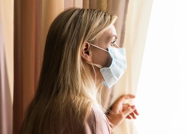 Blonde vrouw sociaal afstand nemen thuis vanwege pandemie