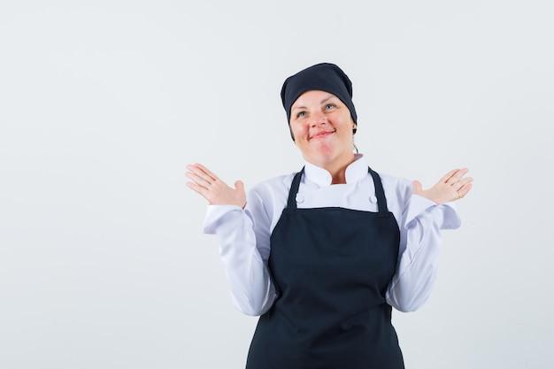 Blonde vrouw spreidende handpalmen als hulpeloos gebaar in zwarte uniforme kok en op zoek gelukkig, vooraanzicht.