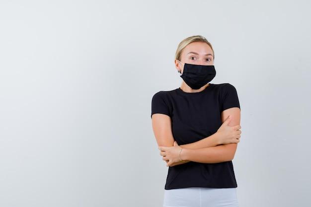 Blonde vrouw staande armen gekruist in zwart t-shirt, witte broek