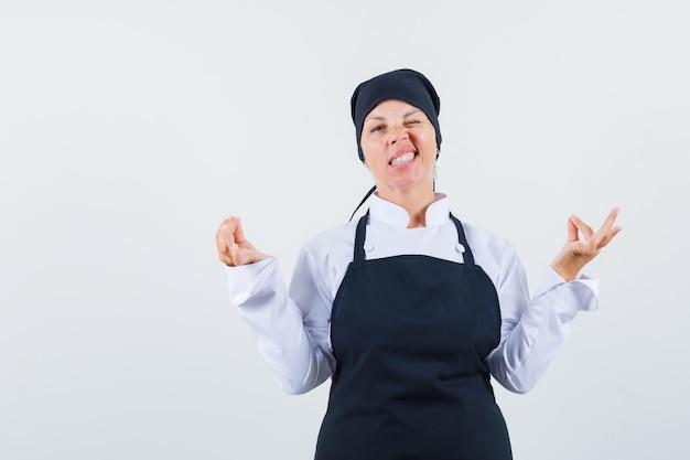 Blonde vrouw staande in mediterende pose, knipoogt in zwarte kok uniform en ziet er mooi uit. vooraanzicht.