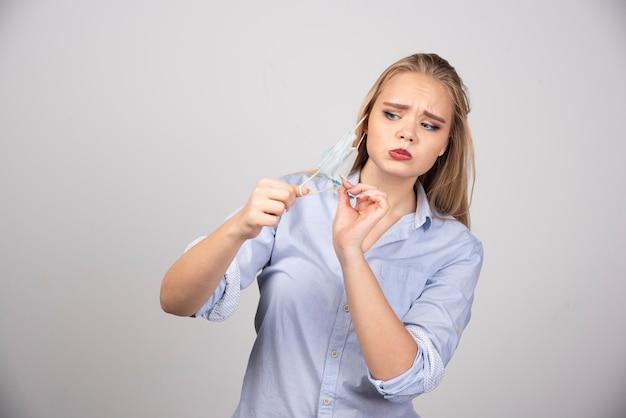 Blonde vrouw staat en draagt een medisch gezichtsmasker.