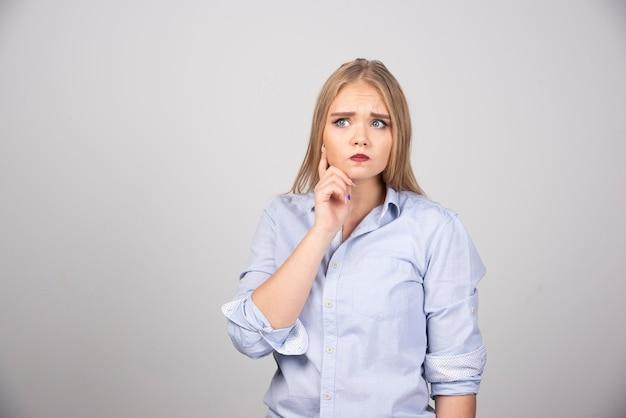 Blonde vrouw staat en kijkt serieus weg tegen de grijze muur.