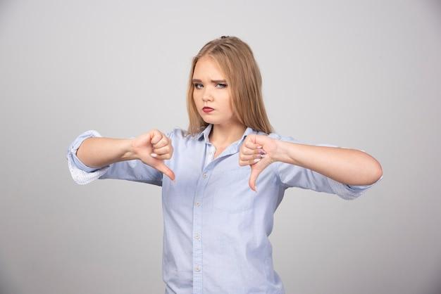 Blonde vrouw staat en toont duimen naar beneden tegen grijze muur.