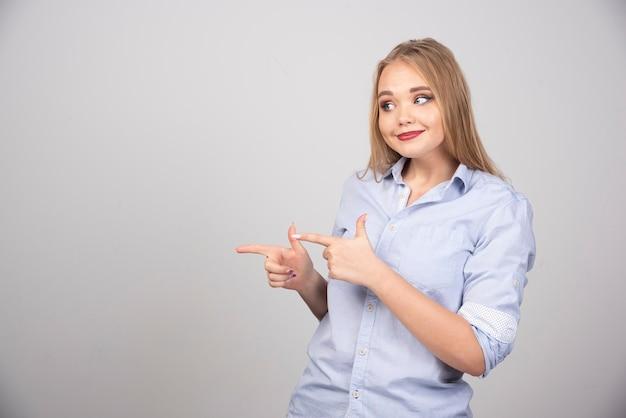 Blonde vrouw staat en wijst met de vingers opzij tegen de grijze muur.