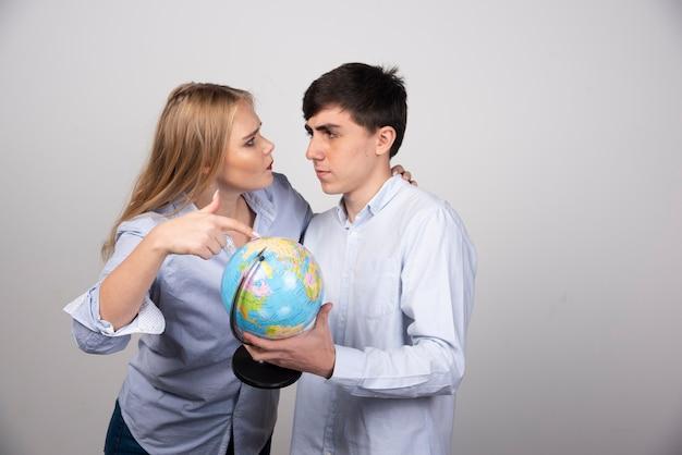 Blonde vrouw staat en wijst naar de aardbol in de buurt van een brunette