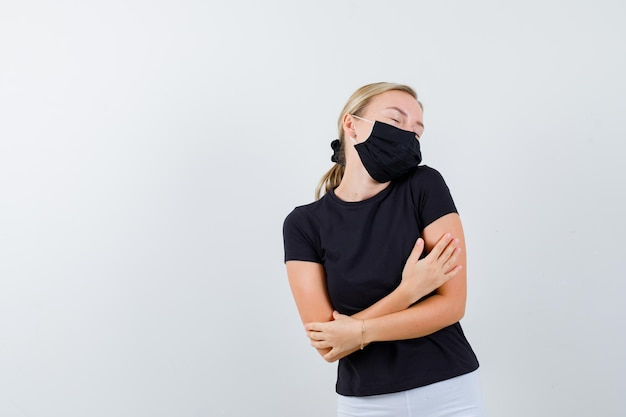 Blonde vrouw staat met haar armen gekruist en omhelst zichzelf terwijl ze poseert in een zwart t-shirt