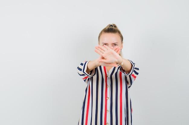 Blonde vrouw stond met gekruiste handen en stop gebaar in gestreepte blouse tonen en serieus kijken