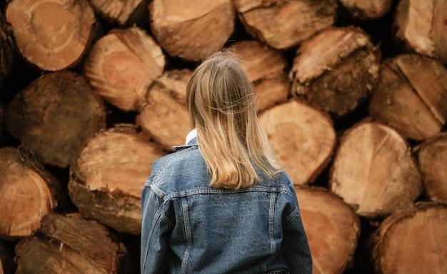 Blonde vrouw stond overdag in de buurt van hout