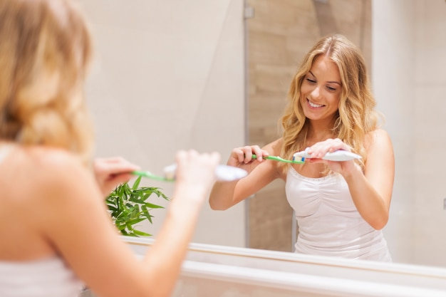 Blonde vrouw tandenpoetsen voor spiegel