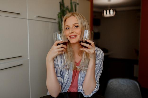 Blonde vrouw tases twee glazen rode wijn in haar eigen keuken.