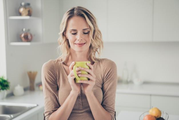 Blonde vrouw thuis in de keuken met koffie