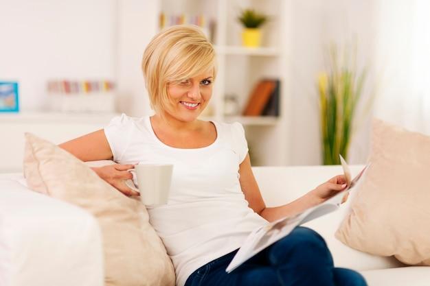 Blonde vrouw thuis ontspannen met koffie en krant