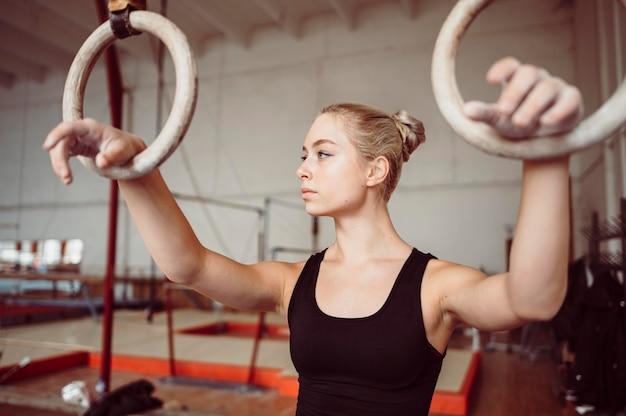 Blonde vrouw training op gymnastiek ringen
