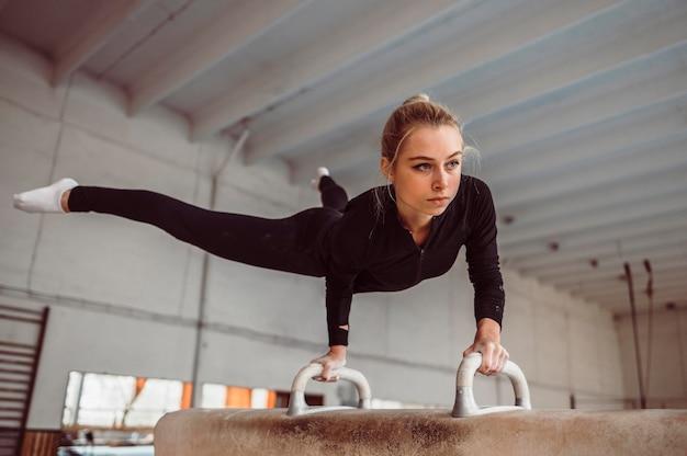 Blonde vrouw training voor kampioenschap turnen