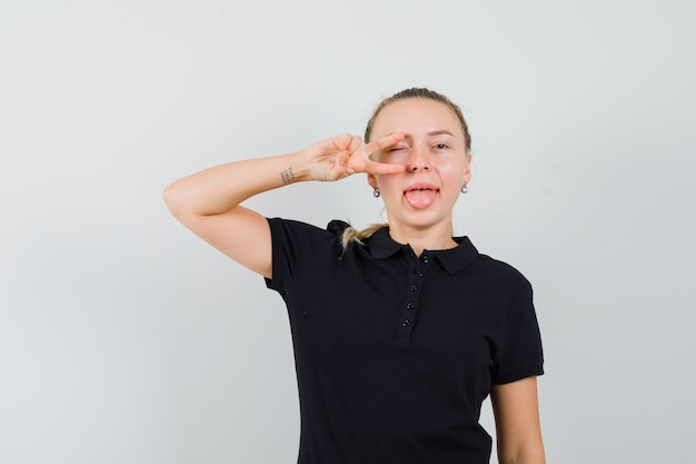 Blonde vrouw v-sign tonen en mond openen met tong uitsteekt in zwart t-shirt en op zoek gelukkig