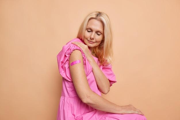 Blonde vrouw van middelbare leeftijd draagt bandje om schouder nadat ze een vaccin heeft gekregen, laat zien dat gevaccineerde arm roze jurk draagt