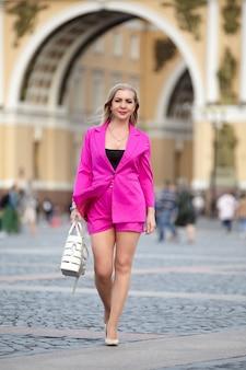 Blonde vrouw van middelbare leeftijd in roze pak loopt in het historische centrum van sint-petersburg, rusland.