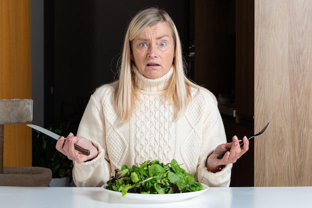 Blonde vrouw van middelbare leeftijd met ontevreden gelaatsuitdrukking salade eten in de keuken, gezonde voeding en dieet concept