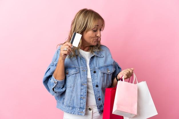 Blonde vrouw van middelbare leeftijd over geïsoleerde roze achtergrond met boodschappentassen en een creditcard