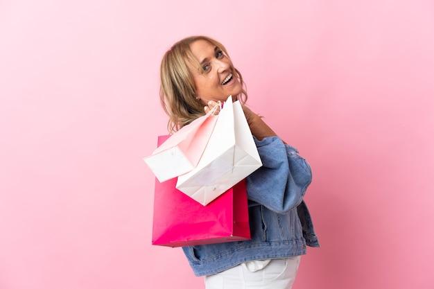 Blonde vrouw van middelbare leeftijd over geïsoleerde roze achtergrond met boodschappentassen en glimlachen