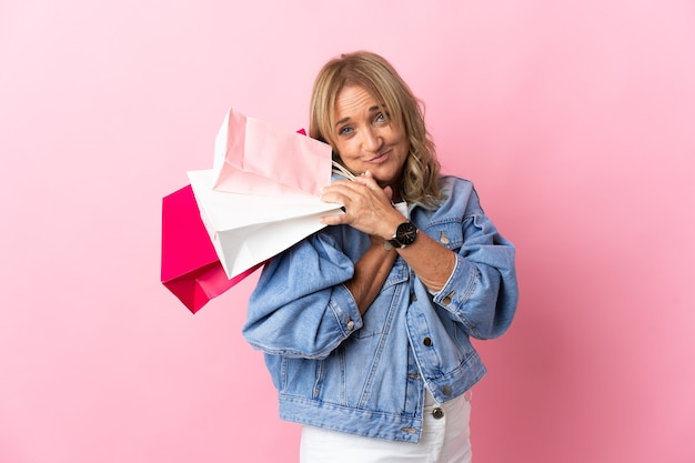 Blonde vrouw van middelbare leeftijd over geïsoleerde roze achtergrond met boodschappentassen